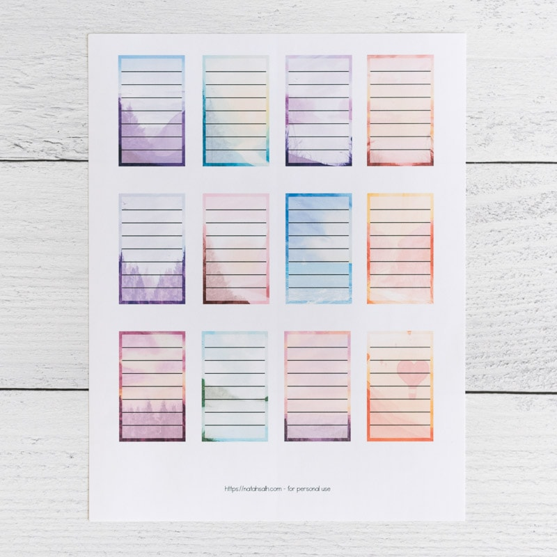 A printed page of 12 full box planner stickers for Happy Planner Classic. Each box has a watercolor landscape background and a translucent white rectangle with seven lines to write on.