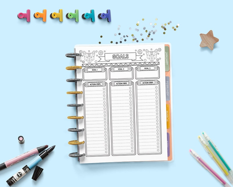 An open Happy Planner disc bound planner with a bullet journal style goals planner page. The page has space to write three goals and break each one down into action steps. The planner is non a blue surface with gel pens, markers, and colorful binder clips.