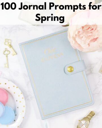"""text overlay """"100 journal prompts for spring"""" over an image of a blue notebook with macrons and pink flowers on a white marble surface"""