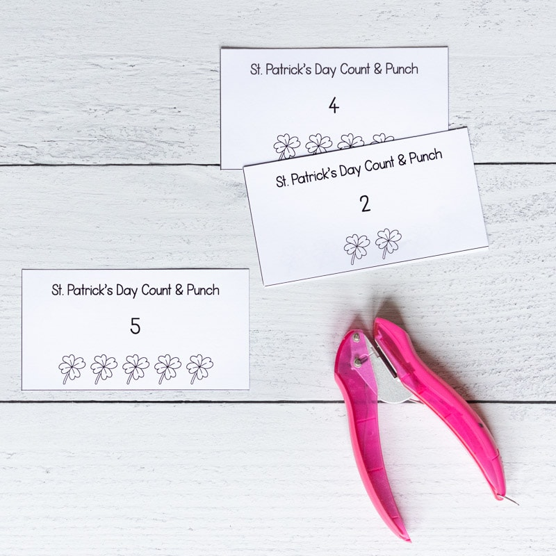 Three printed and cut St. Patrick's Day count and punch cards on a white wood surface with a pink single hole punch