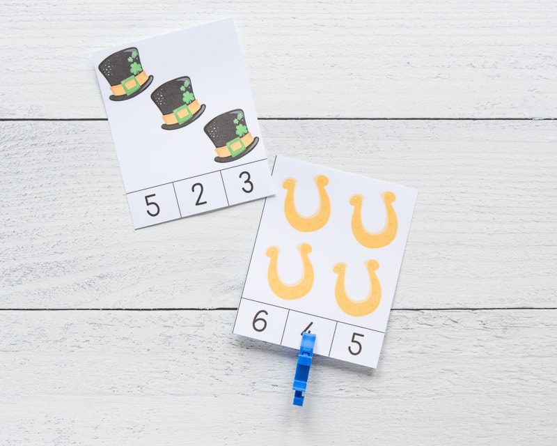 "Two printed count and clip cards with a St. Patrick's Day theme. One card has four gold horseshoes and the number ""4"" is clipped with a blue clip. Next to this card is a card with three black hats."