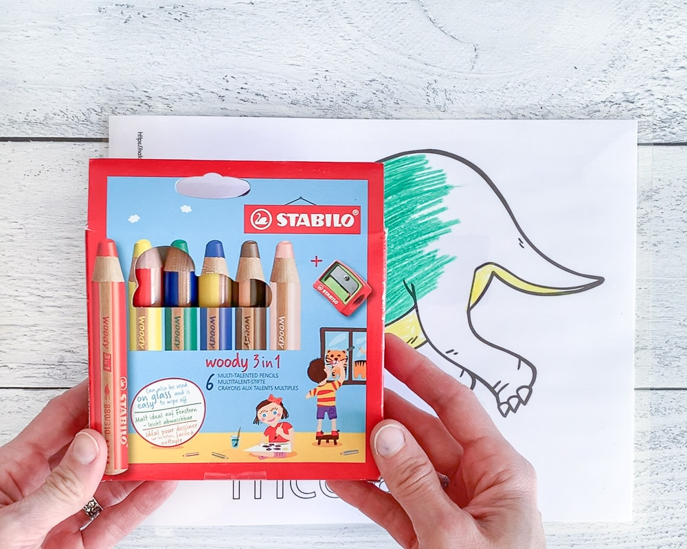 Hands holding a box of 6 Stabilo Woody colored pencils above a partially colored printable page with a triceratops