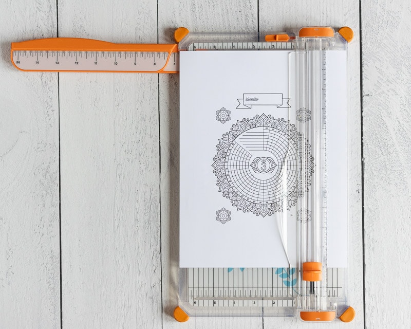 A printable habit tracker on a paper trimmer. The paper trimmer is on a white wood surface.