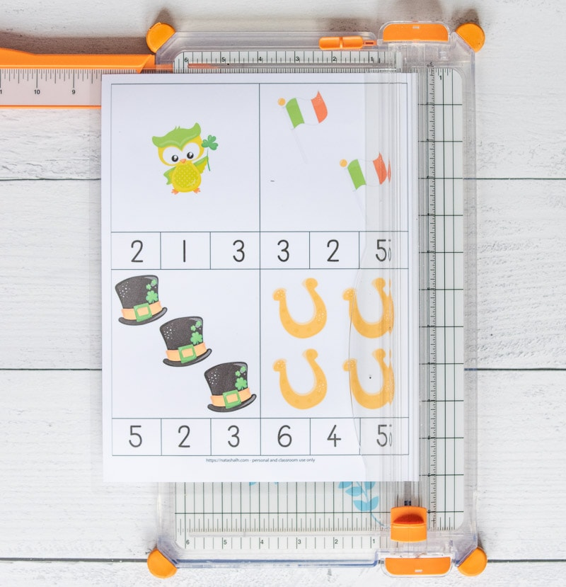 A page with four count and clip cards on a paper trimmer. The cards have St. Patrick's Day images 1-4 with numbers to clip with the correct quantity.