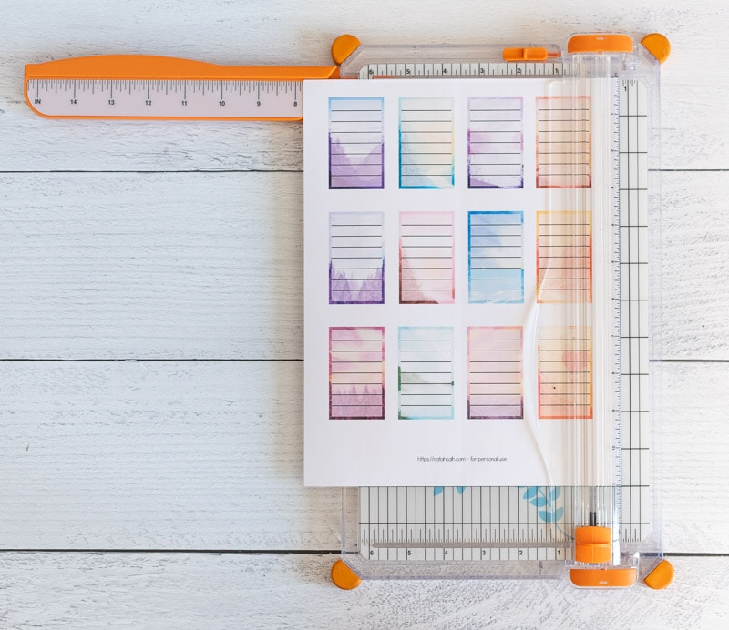 Trimming a page of printable planner stickers with a paper trimmer. The stickers are full boxes for Happy Planner. Each box has a watercolor landscape background and a translucent white rectangle with seven lines to write on.