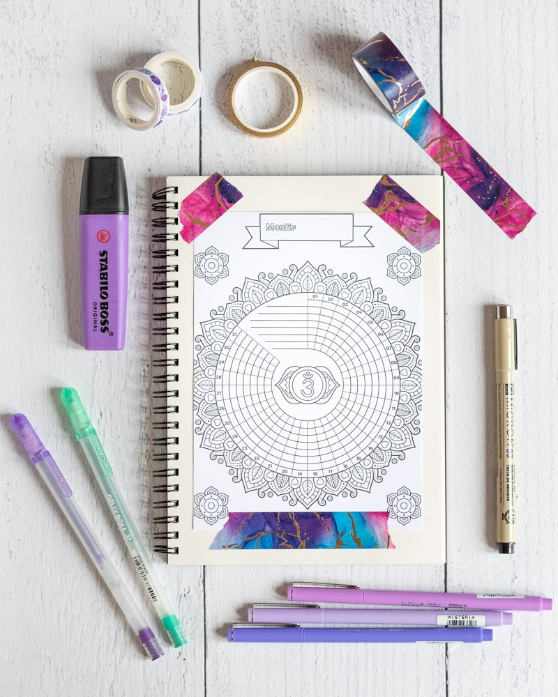 A spiral bullet journal with a charka themed bullet journal printable taped to a page with marveled puree and blue washi tape. The planner is surrounded by offie supplies, including gel pens, a purple Stabilo Boss highlighter, a Micron pens and three purple fineliners.