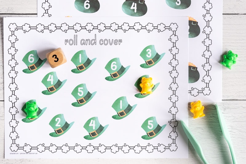 """A printable St. Patrick's Day roll and cover page with 12 green top hats. Each hat has a number 1-6. Two hats have a counting bear covering the number. A wood die showing """"3"""" and a paint of tongs are next to the printable page."""