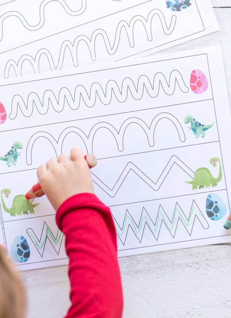 A preschooler's arm in a  red shirt holding a red crayon to trace a dinosaur themed trace in the path page.