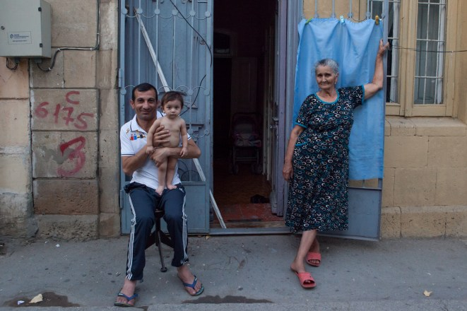 The family resting in front of its home in 'Sovetski' district. In summer the temperature can reach up to 45 C. Not many houses are air-conditioned, so in the evening a lot of people come out to the street for a breath of fresh air and a small talk with their neighbors