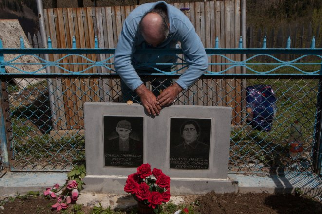 The main reason why Valera and Maro cannot leave the village is that they do not want to abandon their ancestors' graves