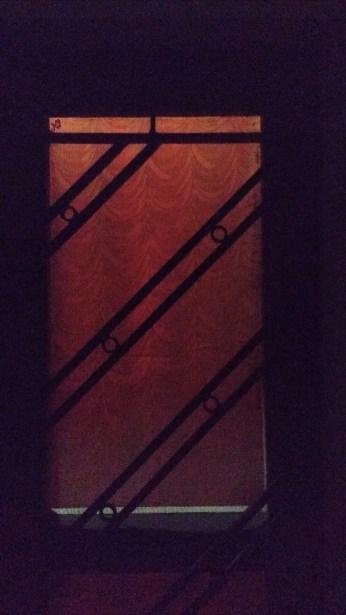 an orange curtain behind window frame