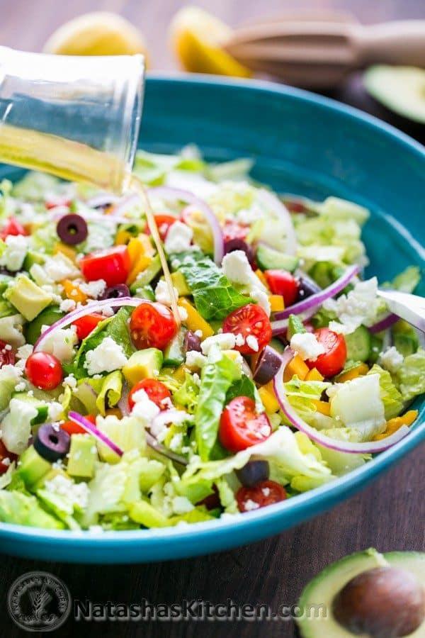 Greek salad dressing pouring onto Greek salad