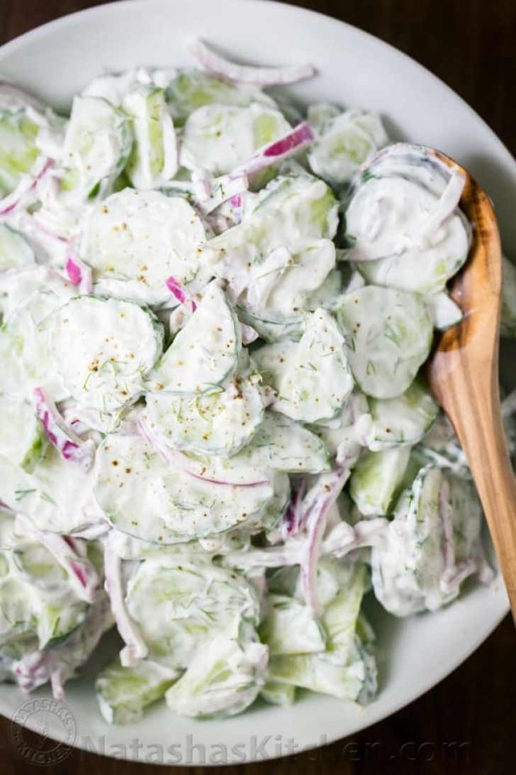 Creamy Cucumber Salad served in a bowl with a wooden spoon