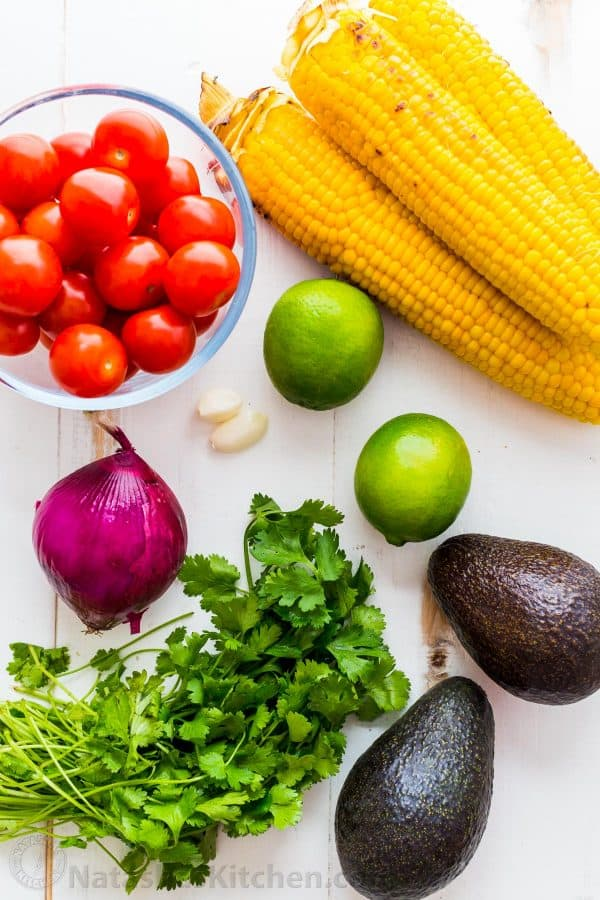 Ingredients for summer corn salad with avocado, tomatoes, cilantro, red onion, garlic and lime juice