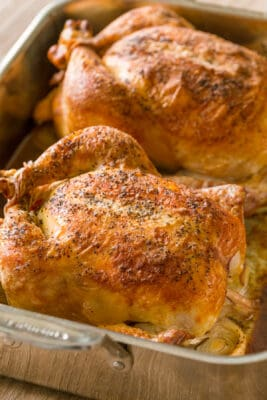 Two roasted chickens in pan