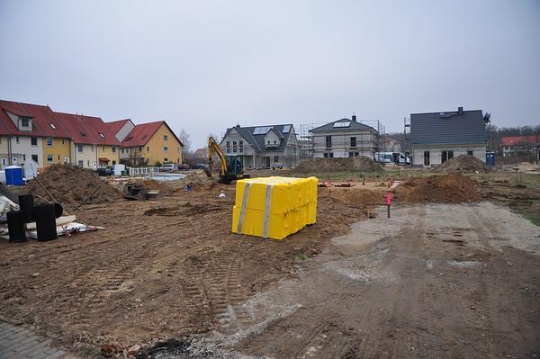 Bauarbeiter heben Gräben für die Abwasserrohre aus. Vorne liegt ein Teil der Perimeterdämmung.