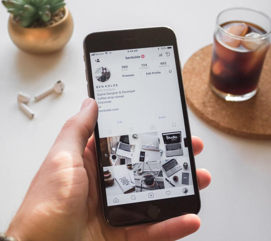 hand holding a mobile phone showing an instagram account and in the background is a cup of coffee and a small desk plant