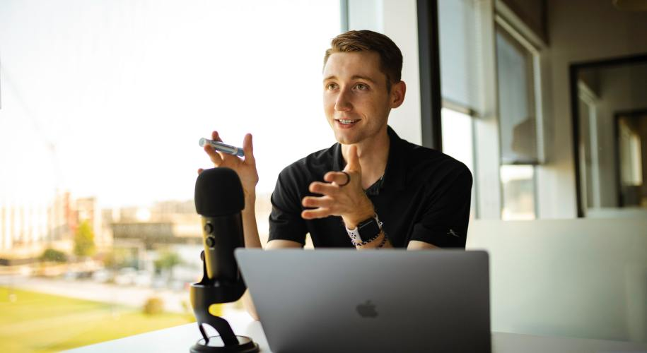 man sitting in front of microphone and laptop talking