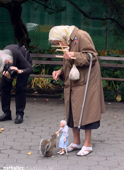 Older woman in a park with a marionette of herself that feeds a squirrel. A women next to her taking a photo of the scene