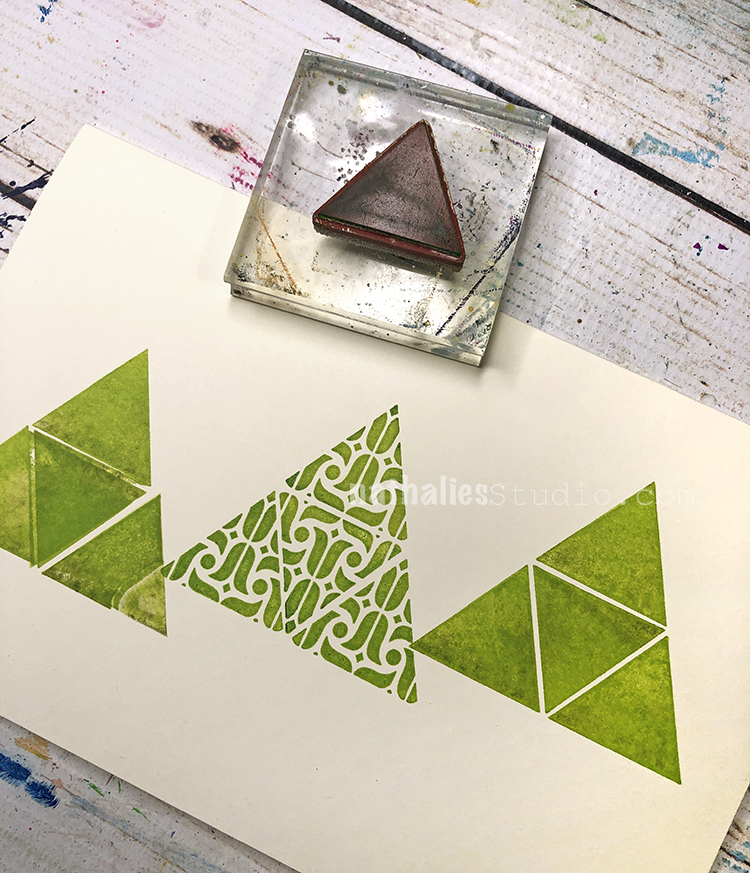 three hand stamped triangle shapes in a row with a triangle rubber stamp