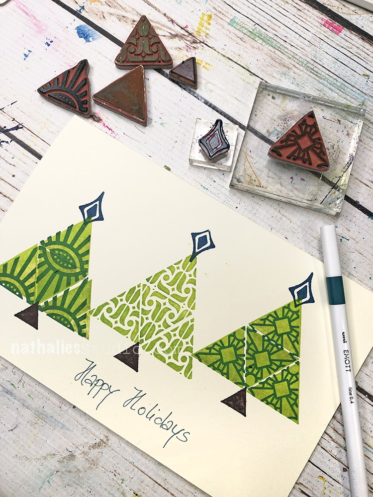 handmade card with triangle shaped trees with toppers, besides the card some triangle shaped and patterned rubberstamps that were used to create the card.