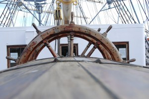 Photograph of a ship's wheel.