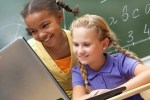 two young girls at a laptop