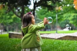 Young girl catching bubble