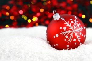 9156-a-red-christmas-ornament-in-the-snow-with-lights-in-the-background-pv