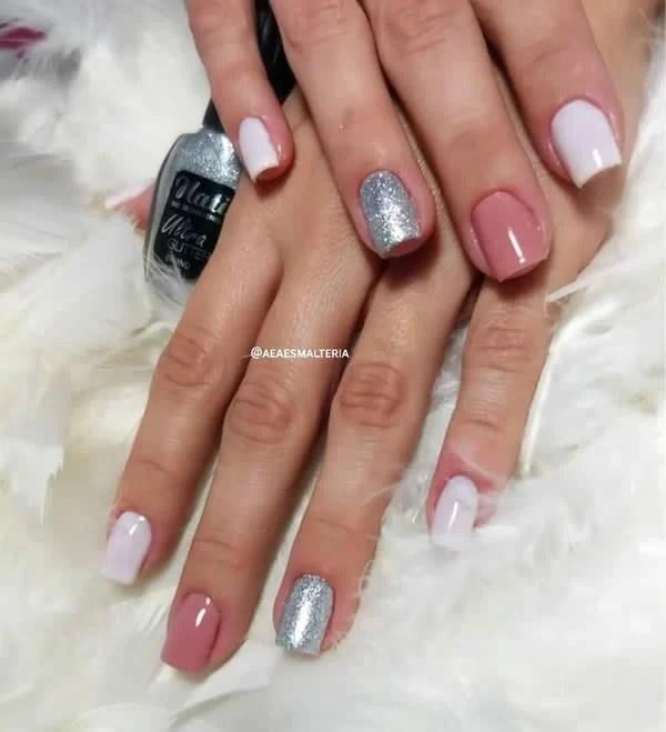 unhas decoradas curtas e quadradas, com dois dedos de branco, um de rosa nude e ouro de glitter prata