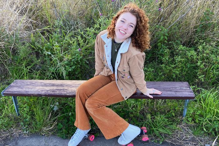 Emily sitting on a park bench wearing roller-skates.