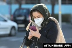 """An Iranian woman checks messages on her smart phone in Tehran. """"It's like [authorities] are determined to fight the people.... [They] are happy about the torment they are inflicting on Iran,"""