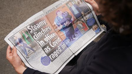 A person reads a copy of the Sun newspaper in Westminster, London, with the story and pictures of He
