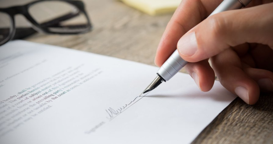Image of Hand Signing Letter