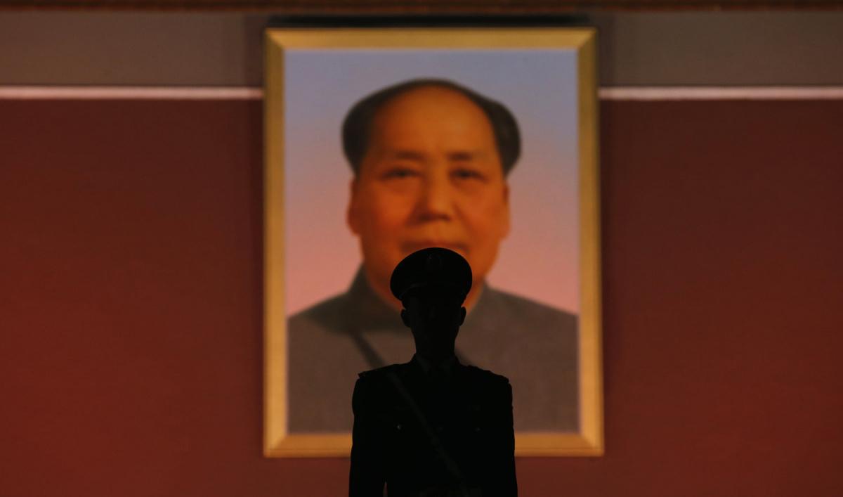 Un policier paramilitaire monte la garde devant le portrait géant du défunt président chinois Mao Zedong à l'entrée principale de la Cité Interdite à Beijing, le 28 octobre 2013. Cinq personnes ont été tuées et des douzaines blessées lundi, selon le gouvernement, lorsqu'une voiture enfoncé dans les piétons et a pris feu sur la place Tiananmen de Pékin, le site des manifestations pro-démocratiques de 1989 réprimées par l'armée. La voiture s'est écrasée presque directement devant l'entrée principale de la Cité Interdite, où