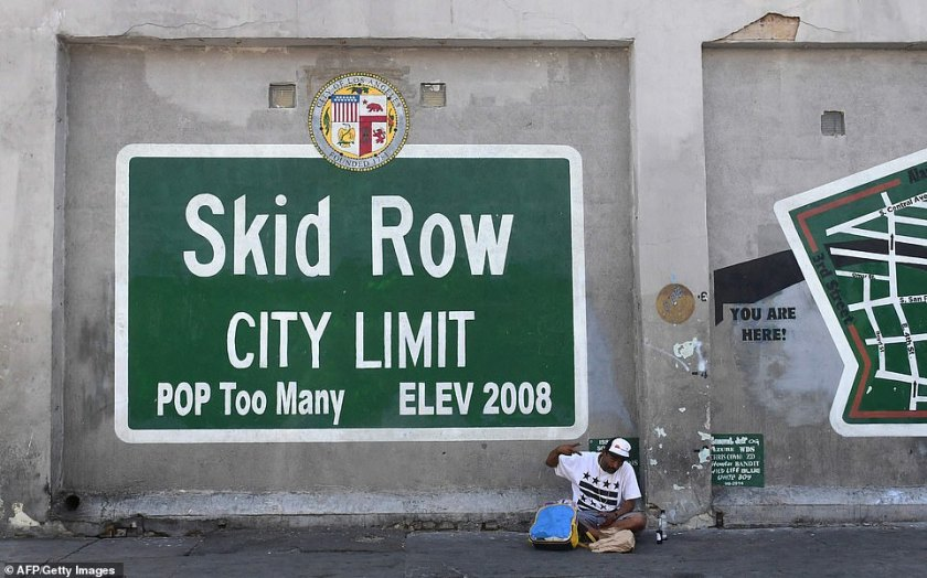 A man gestures while seated beside a Skid Row painting on a sidewalk in downtown Los Angeles