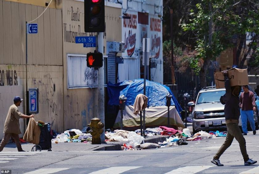 The union that represents the LAPD is demanding a cleanup of homeless encampments in the city after one detective who works downtown was diagnosed with typhoid fever and two others are showing similar symptoms. Pedestrians cross a street lined with trash near LAPD Central Community Police Station in downtown Los Angeles on Thursday