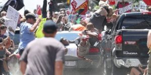 A grey car drives into a crowd of protesters carrying colorful signs, sending two men airborne while onlookers rush to the scene