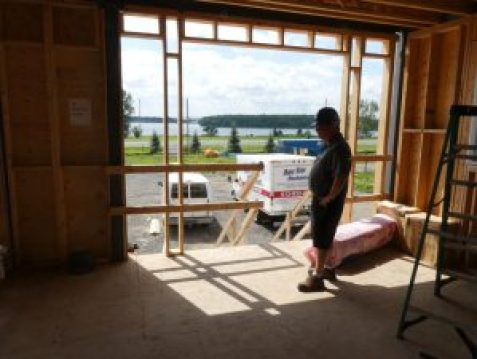 Henri Lecours looks out one of the south-facing windows, toward the St. Lawrence River. Zandbergen photo, Nation Valley News