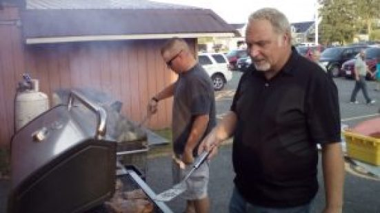 Councillor Al Armstrong (foreground) assists with barbecue duty at the Morewood event. Zandbergen photo, Nation Valley News