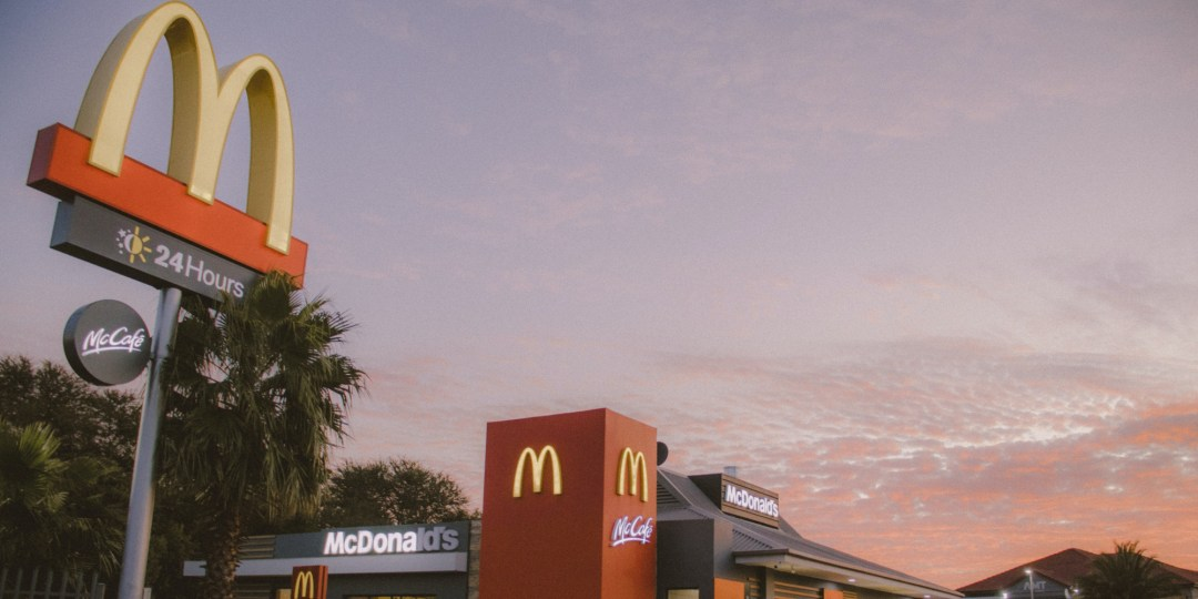 24-hour McDonald's with drive-thru in front of a pink/rose sky
