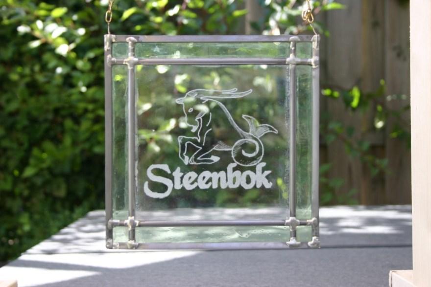 Glas in lood raamhanger met gegraveerde steenbok horoscoop in het midden, rand is van blank glas.