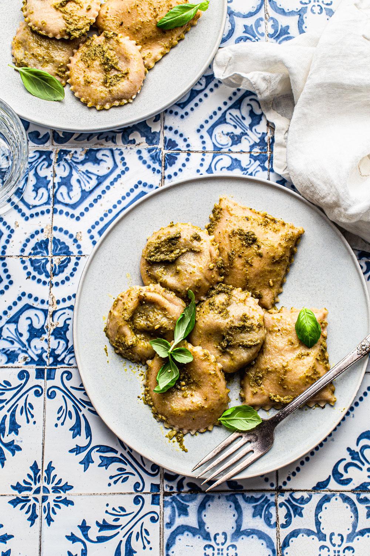 Vegan Mushroom Ravioli with Pesto on a blue tile backdrop foo photography