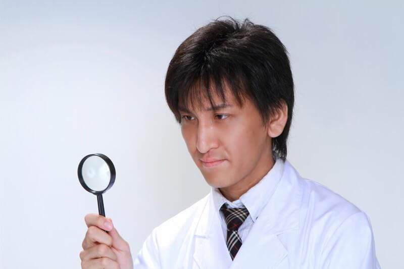 虫眼鏡で調べる男性