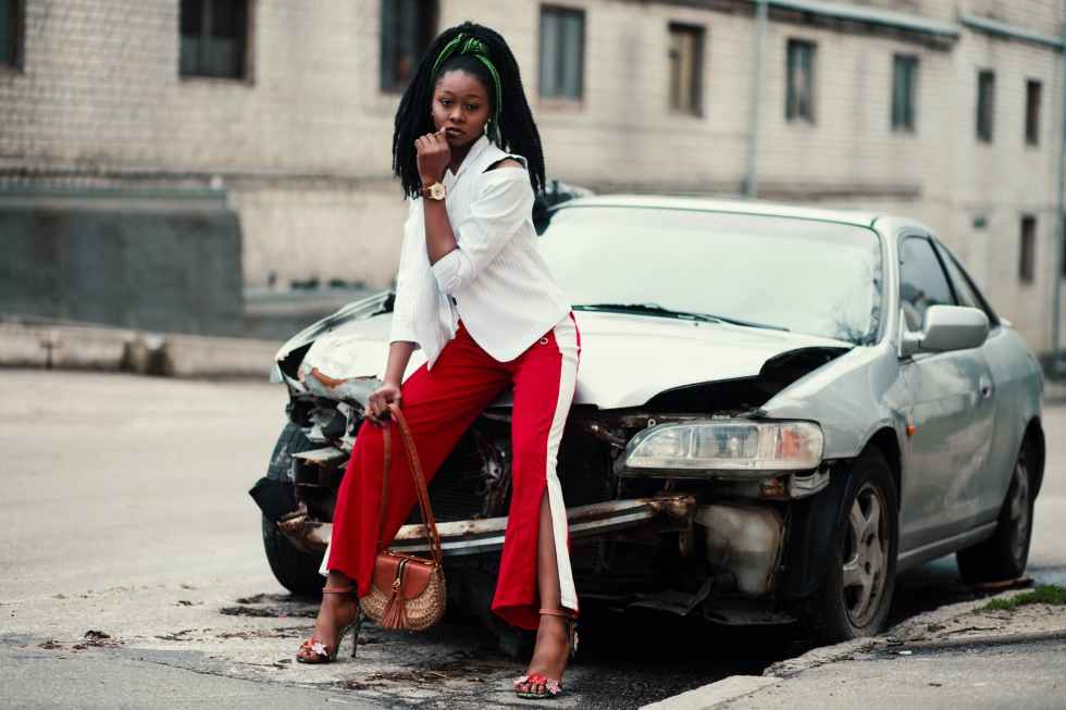 woman with white long sleeved shirt red and white slit pants and pair of black open toe d orsay heel sandals sitting on wrecked silver car