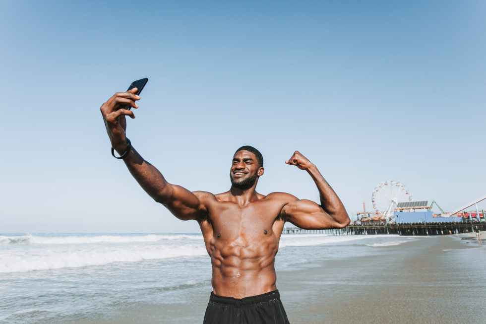 standing man on seashore taking selfie