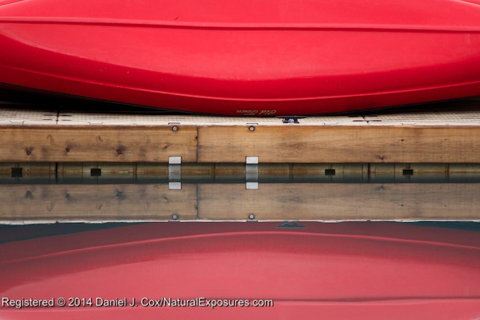 A mirror image of the red Old Towne canoe on the dock at Lake Louise. GH4 with 45-175mm zoom. ISO 1000