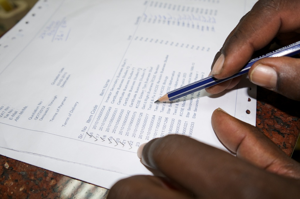 Henry checks each title and ticks them off as they are run through purchase process. Kenya, Lumix LX100