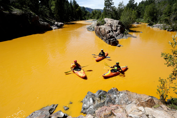 People kayaking in the Animas River near Durango, Colo., last Thursday, in water colored from a mine waste spill. The river is now closed indefinitely, with visitors warned to stay out. Credit Jerry Mcbride/The Durango Herald, via Associated Press