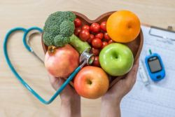 diabetic friendly foods: Image of hands holding a bowl of fruits with a blood glucose monitor and stethoscope in the background.